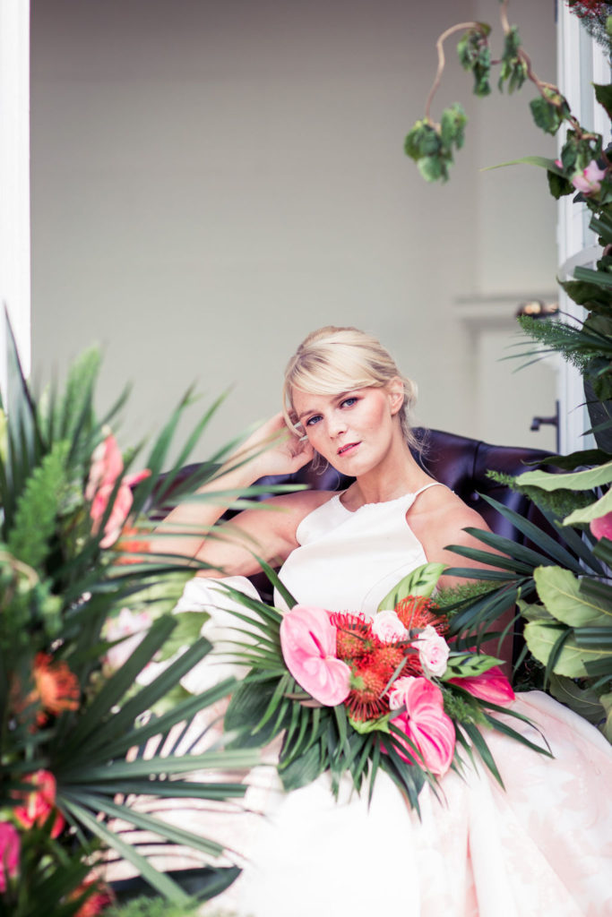 bride seated in armchair surrounded by tropical plants and flowers