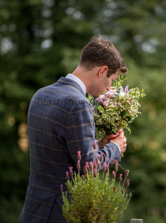 groom smelling bouquet of flowers