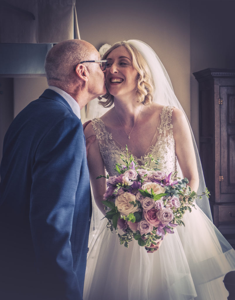 bride holding wedding bouquet is kissed by her father